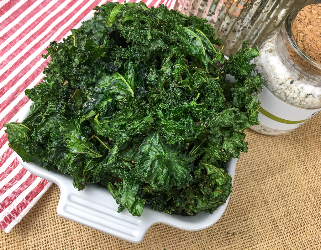 Crispy kale chips in a white serving dish.
